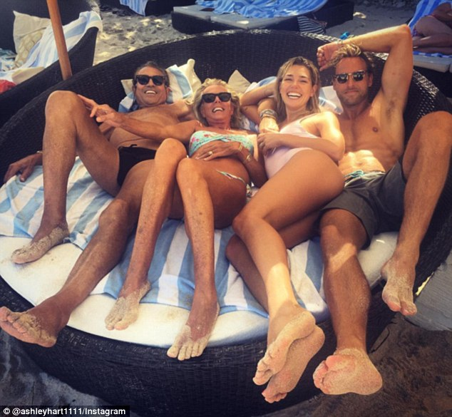 Lounging around: The blonde beauties were snapped again in their swimwear laying on a sun lounger, squished in with their respective husbands beside them