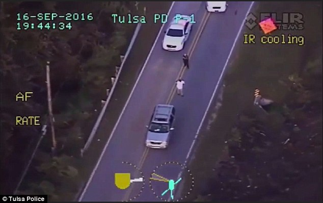 Crutcher, pictured in the white shirt being filmed by a Tulsa Police helicopter after his car broke down in the middle of the road on Friday night, was shot dead shortly afterwards