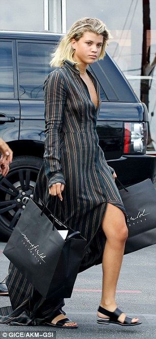 Girl time: The petite blonde wore a very plunging long striped shirt dress and some black sandals as she was seen carrying some shopping bags
