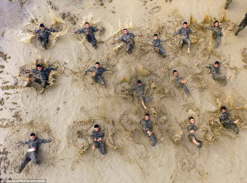 Harsh and brutal conditions: The men can be seen moving around in the mud as part of their training regime