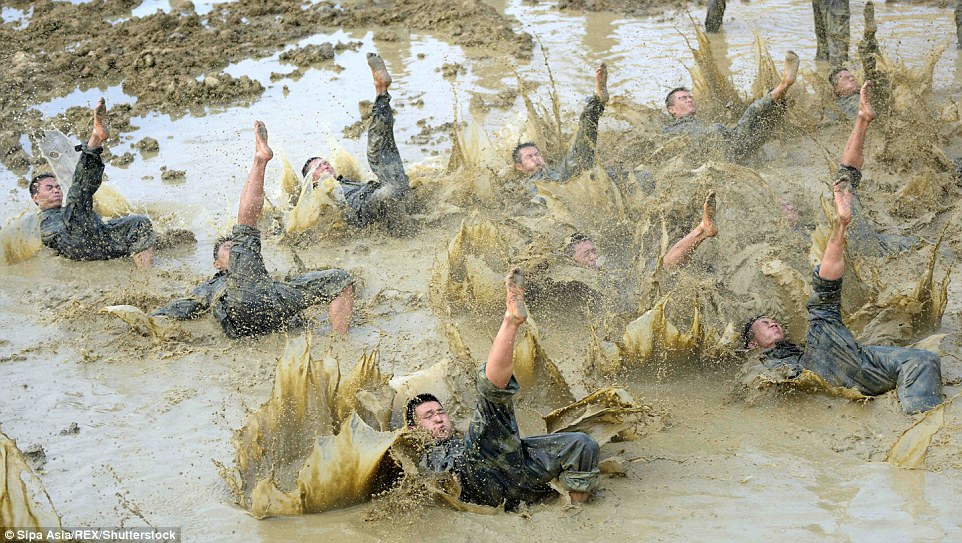 Kicking around in the mud: The men kick their feet around in the mud during their brutal police training exercises