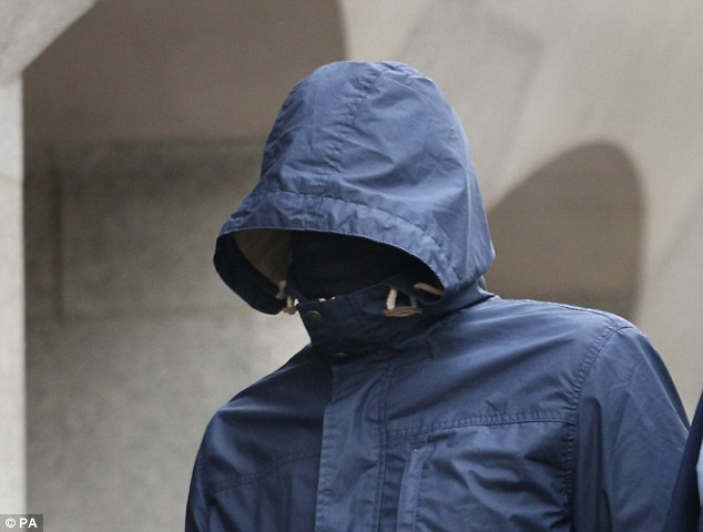 Approaching the Old Bailey: Mahmood arrived outside court this morning flanked by two bodyguards with the hood of his navy blue anorak pulled up and his face covered