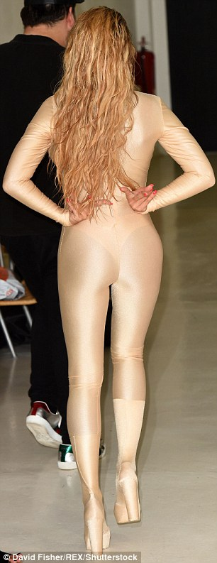 Wet and wild: Her long wavy hair threatened to soak every part of her skintight ensemble that it came into contact with