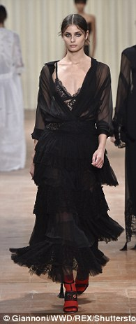 Gothic glamour: Dark colours andwhimsical fabrics made up the show as the models stormed the runway in black and purple sheer fabrics adorned with lace and ruffles
