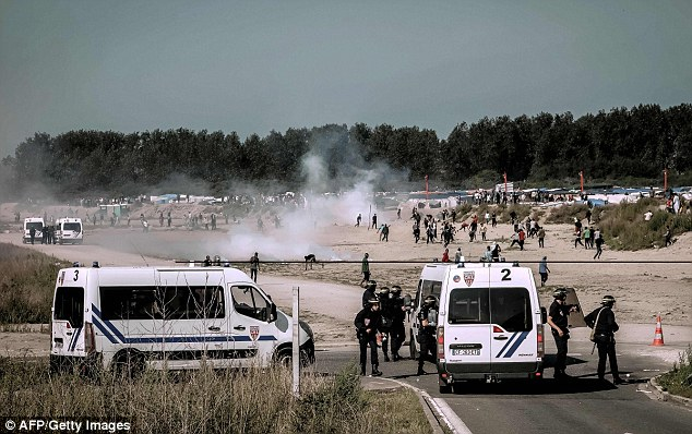 Riot police disperse migrants with tear gas today as they tried to get into lorries heading to Britain