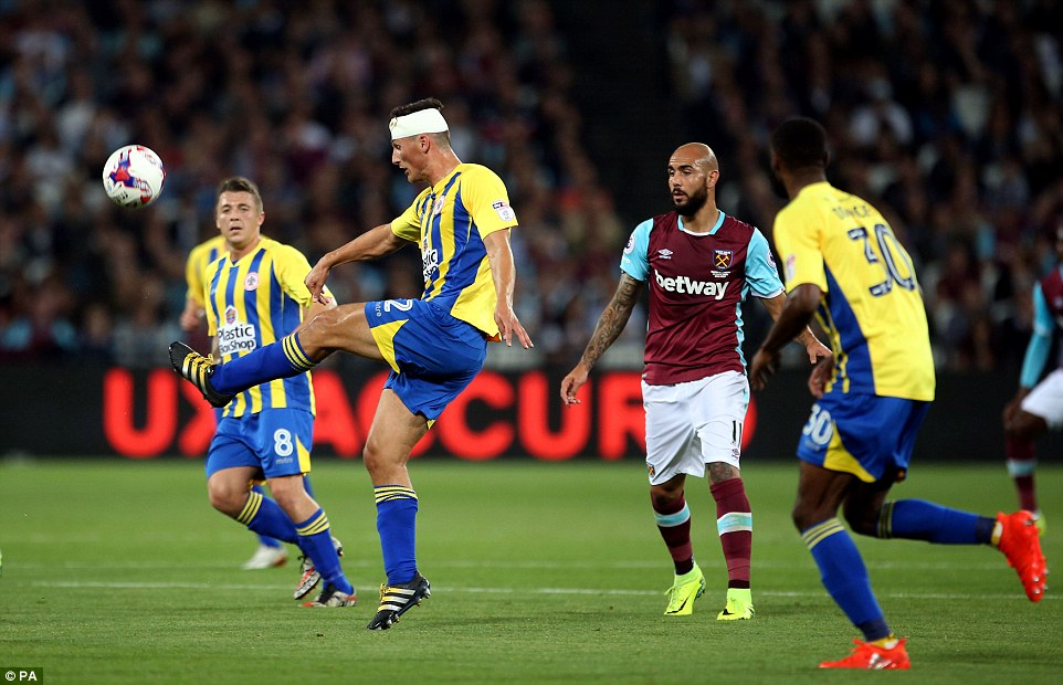 A bandaged up Pearson completes a clearance for Accrington with West Ham's Simone Zaza in the close attendance