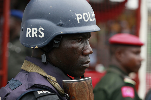 FILE- In this Thursday, May. 1, 2014 file photo, a police officer stand guards during a demonstration in Lagos, Nigeria. An elite Nigerian police squad set u...