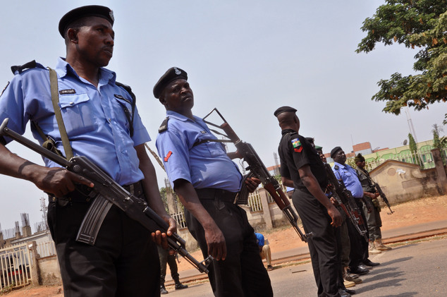FILE- In this Saturday Feb. 7, 2015 file photo Nigeria police officers block a road in the city of Abuja, Nigeria. An elite Nigerian police squad set up to c...