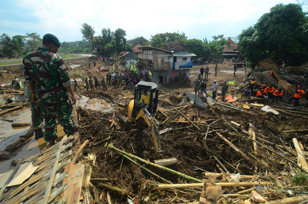 Rescuers search through debris for victims in a village badly hit by a flash flood in Garut, West Java, Indonesia, Wednesday, Sept. 21, 2016. Torrential rain...