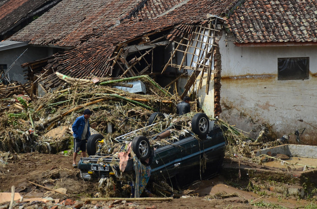 A man inspects a damaged vehicle in a village badly hit by a flash flood in Garut, West Java, Indonesia, Wednesday, Sept. 21, 2016. Torrential rains triggere...