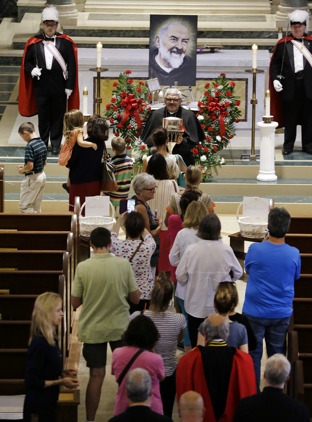 People line up to venerate the heart of St. Padre Pio held in a plastic box by a priest at the Immaculate Conception Church, Wednesday, Sept. 21, 2016, in Lo...