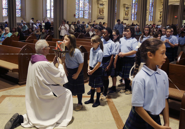 The heart of St. Padre Pio, held in a plastic box by a priest, is kissed by a schoolgirl at the Immaculate Conception Church, Wednesday, Sept. 21, 2016, in L...