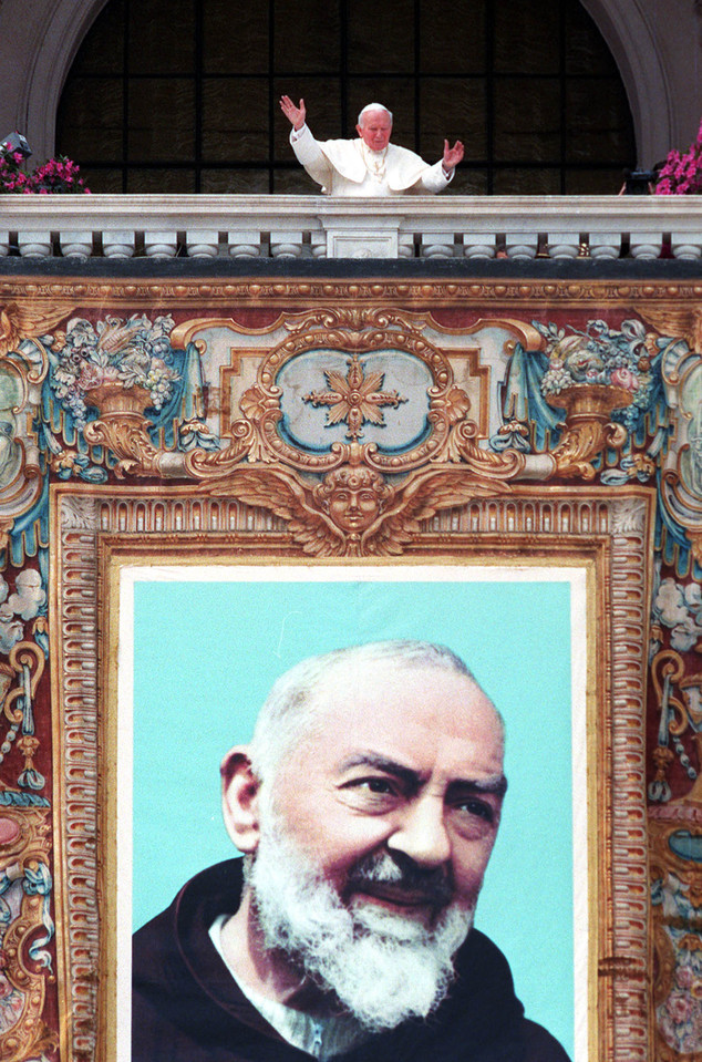 FILE - In this May 2, 1999 file photo, Pope John Paul II acknowledges the faithful above the tapestry of Italy's most famous Capuchin monk Padre Pio, hung on...