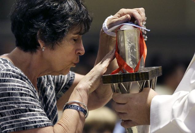 The heart of St. Padre Pio held in a plastic box by a priest is touched by a woman at the Immaculate Conception Church, Wednesday, Sept. 21, 2016, in Lowell,...