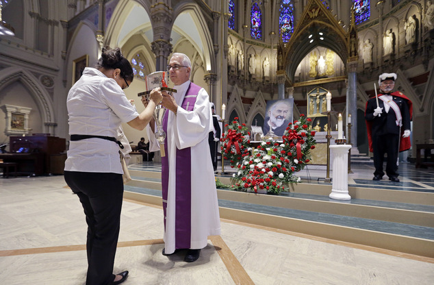 A woman bows her head at the heart of St. Padre Pio, held in a plastic box by a priest, during veneration at the Immaculate Conception Church, Wednesday, Sep...