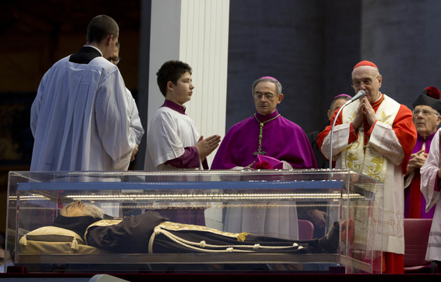 FILE - In this Feb. 5, 2016 file photo, Cardinal Angelo Comastri, right, prays in front of the box containing the corpse of Saint Pio da Pietralcina laid in ...