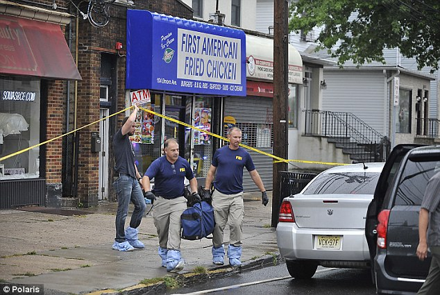 Police and FBI bring items out of the apartment above the First American Fried Chicken restaurant, both owned and lived in by the family of the Manhattan and New Jersey bomber, on Monday