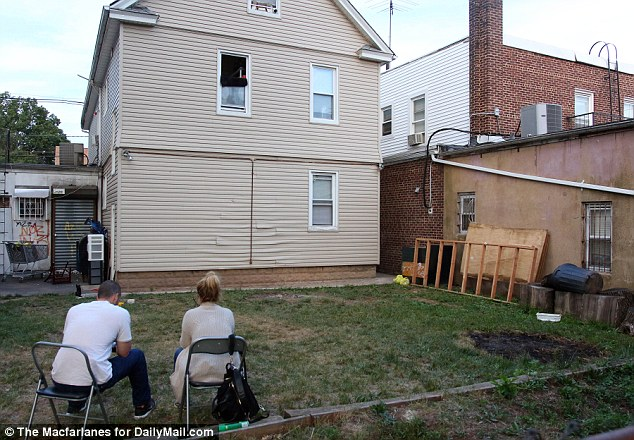 Police officers guard the back garden of Ahmad Rahami's family home on Wednesday as the investigation in Elizabeth, New Jersey continues