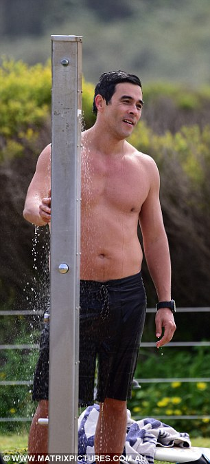 Drying off: James cracks a smile while drying off with a towel after having a beach-side shower on set at Palm Beach