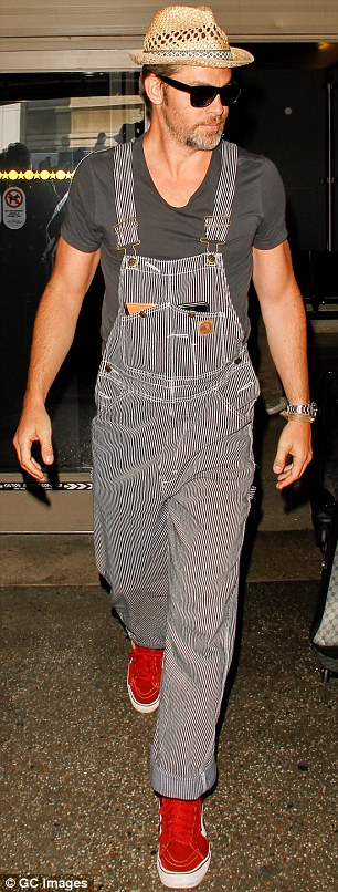 Hipster: Landing back in LA Chris looked to have embraced a more relaxed and bohemian sartorial streak, with the actor emerging from arrivals in a pair of stripy Carhartt overalls