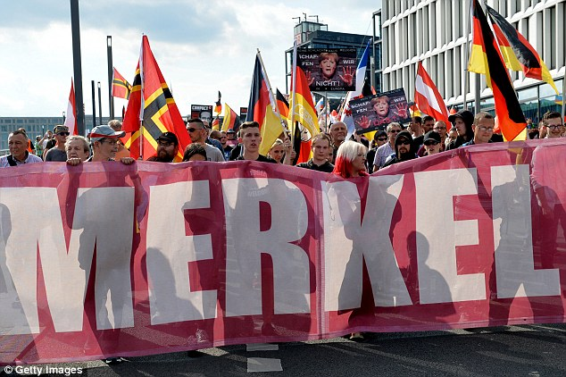 A study carried out by a Christian organisation found 57 per cent of those questioned were concerned about the increasing prominence of the religion in the country.: Demonstrators are pictured in Berlin to protest against German Chancellor Angela Merkel's refugee policy