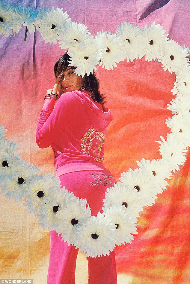 Best asset: Her famous derriere is surrounded by a white daisy chain heart as she strikes a pose in a pink Juicy Couture tracksuit in another photo for the magazine