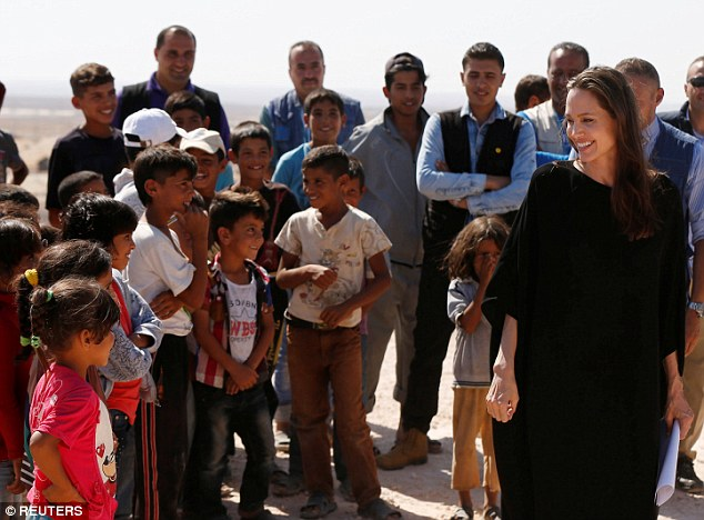 Keeping it simple:Jolie wore a black dress as she laughed and smiled with Syrian children displaced by the conflict