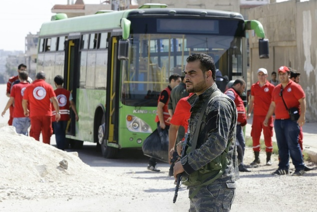 A Syrian soldier stands guard as Red Crescent members wait for opposition fighters and their families to change buses at a Syrian army checkpoint on the edge...