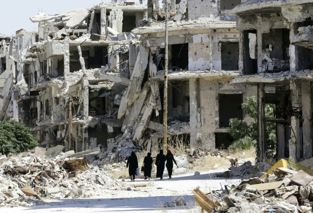 Syrian women walk in between destroyed buildings in the government-held Jouret al-Shiah neighbourhood of the central Syrian city of Homs on September 19, 2016