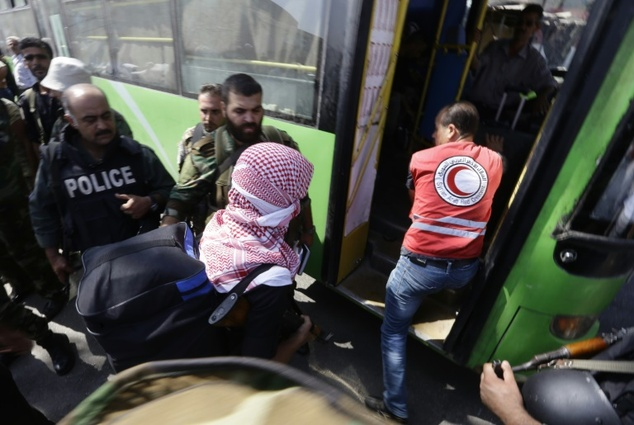 Syrian policemen stand guard as Red Crescent members help opposition fighters and their families carry their belongings onto a bus at a Syrian army checkpoint