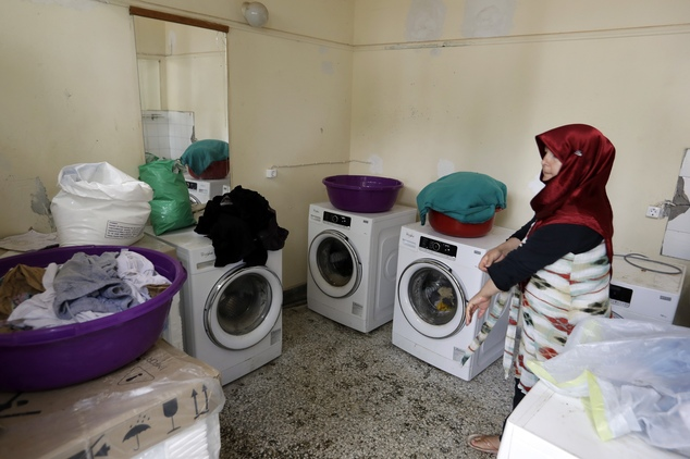 An Afghan woman uses the washing machines at a refugee camp in the western Athens' suburb of Schisto, on Thursday, Sept. 22, 2016. Most of the roughly 60,000...