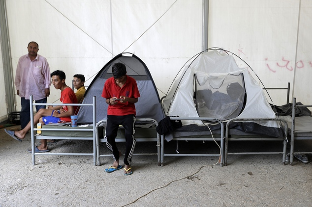 A boy uses his cell phone as the other members of his family sit inside a giant tent at a refugee camp in the western Athens' suburb of Schisto, on Thursday,...