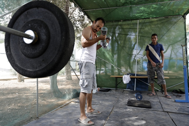 An Afghan man uses a makeshift gym at a refugee camp in the western Athens' suburb of Schisto, on Thursday, Sept. 22, 2016. Most of the roughly 60,000 refuge...