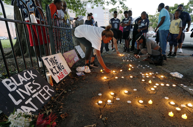 FILE - In this Thursday, Sept. 15, 2016, file photo, community members light candles in memory of 13-year-old Tyre King, shot and killed by a police officer ...