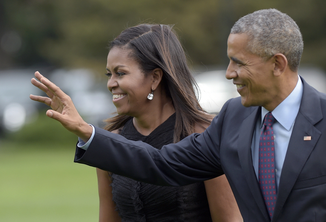 President Barack Obama, with first lady Michelle Obama, waves as they walk from Marine One on the South Lawn of the White House in Washington, Wednesday, Sep...
