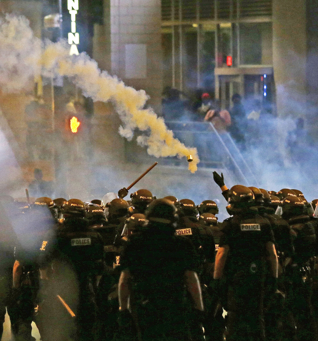 Police fire tear gas as protestors converge downtown following Tuesday's police shooting of Keith Lamont Scott in Charlotte, N.C., Wednesday, Sept. 21, 2016....