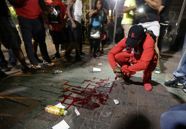 A man squats near a pool of blood after a man was injured during a protest of Tuesday's fatal police shooting of Keith Lamont Scott in Charlotte, N.C. on Wed...