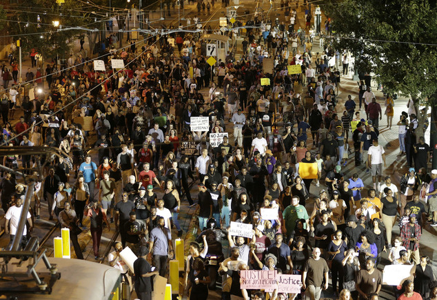Demonstrators protest Tuesday's fatal police shooting of Keith Lamont Scott in Charlotte, N.C. on Wednesday, Sept. 21, 2016. Protesters rushed police in riot...