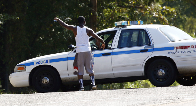 A resident gestures to a policeman as a police presence remains in a south Jackson, Miss., neighborhood, Thursday, Sept. 22, 2016, while lawmen continue to n...
