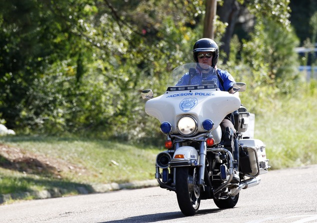 A motorcycle police officer rides along a cordoned-off street in a south Jackson, Miss., neighborhood, Thursday, Sept. 22, 2016, as lawmen continue to negoti...