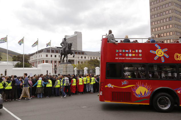 A red bus used by tourists to explore areas around Cape town, passes students and representatives, left, from the University of Cape Town, UCT, as they prote...