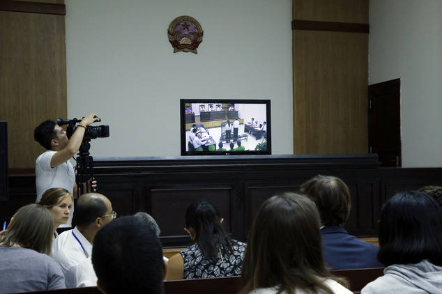 Media and diplomats watch a live screen showing prominent blogger Nguyen Huu Vinh, right, and his colleague Nguyen Thi Minh Thuy, left, in an appeals court i...