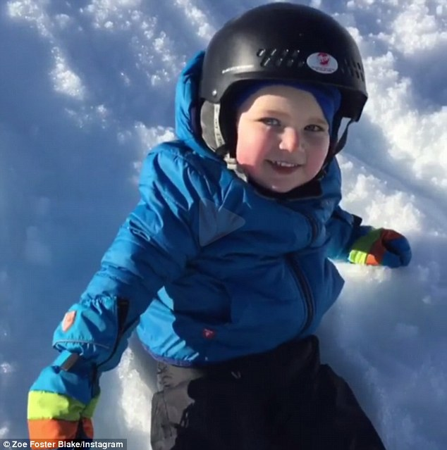 Rugged up:The cherub-like son wore a blue, puffy snow jacket, striped mittens and a black helmet while he slid down the snow with father, Hamish