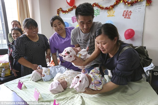 Loving family: The parents take a look at their four baby girls in Shanghai, China