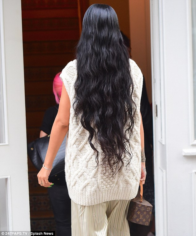Natural beauty:Her long raven-coloured tresses were worn down into waves flowing over her back and she accessorised with a classic Louis Vuitton bag