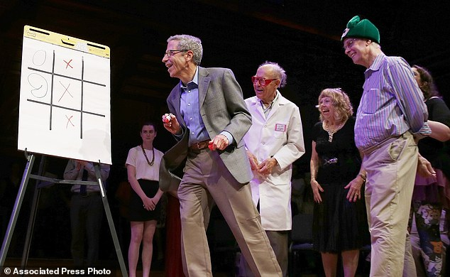 Nobel laureates Rich Roberts (physiology or medicine, 1993), right, Dudley Herschbach (chemistry, 1986) third from right, and Eric Maskin (economics, 2007), second from left, compete in a game of noughts and crosses or tic-toc-toe with a brain surgeon