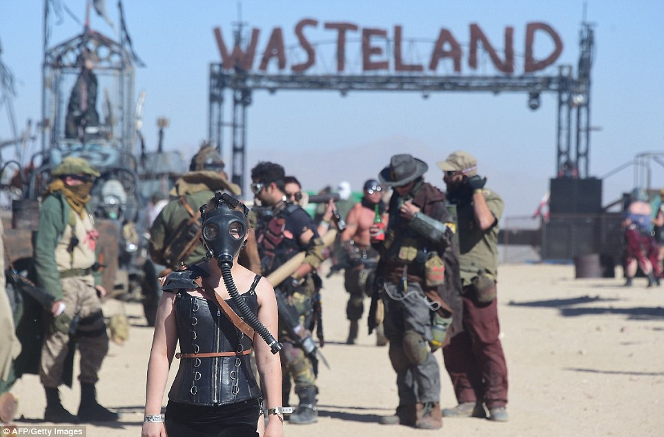 A woman in a leather corset, wears a black gas mask over her face as men stand drinking in the background