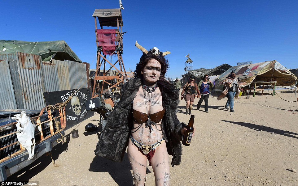 A women dressed in burgundy underwear, a fur coat and plenty of jewelry arrives at the Wasteland Weekend festival with horns on her head