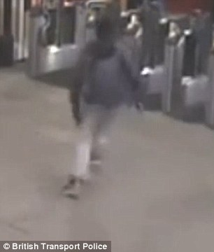 Knife in hand the man runs after his two attackers who escape back through the ticket barriers (pictured)