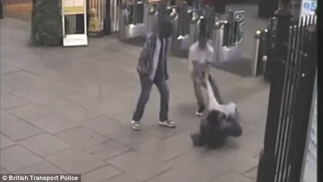 He is then dragged along the floor by his leg by one of the attackers while the other looks on (pictured) during the attack at 7.15pm on August 25